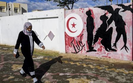 Une Tunisienne marche près d'un mur sur lequel un graffiti représente un homme en en oiseau symbolisant la liberté, le 27 octobre 2020 (AFP)